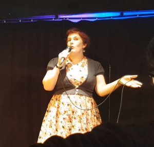 image of a woman with red hair in a yellow dress with a black cardigan holding and speaking into a microphone., arm outstretched.