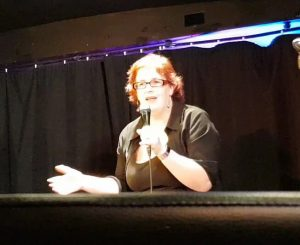 image of kitty fitton, a woman with red hair in a black outfit talking into a microphone with one arm outstretched.