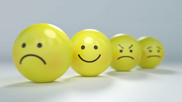 yellow balls in a line with different faces drawn on them. Sad, happy, cross and indifferent.