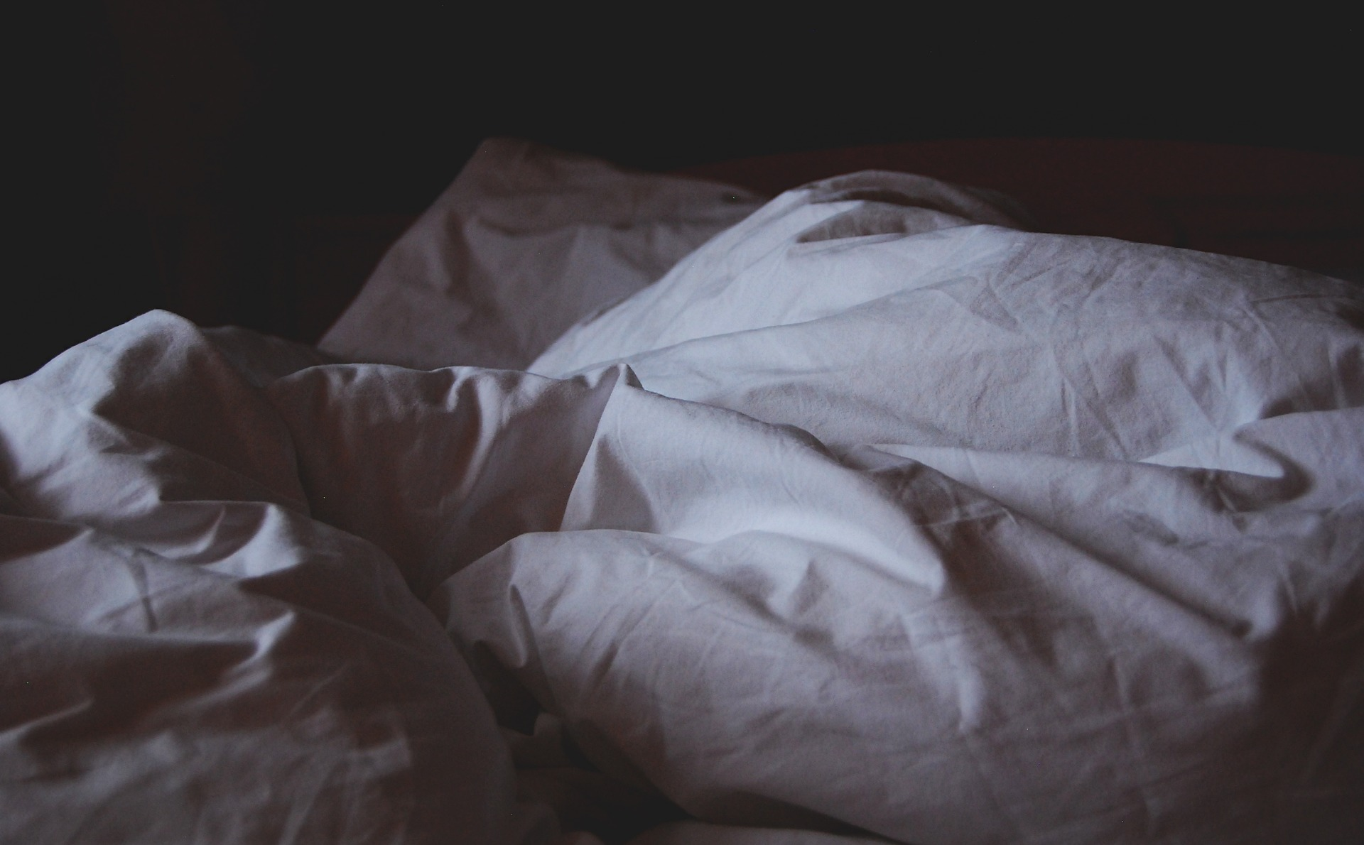 an unmade bed with a white quilt in a dim room.