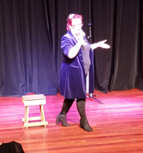 Kitty Fitton wearing a long purple coat and tall boots walking across the floor talking into a microphone.