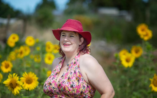 image of kitty in a red hat in a field of sunflowers.