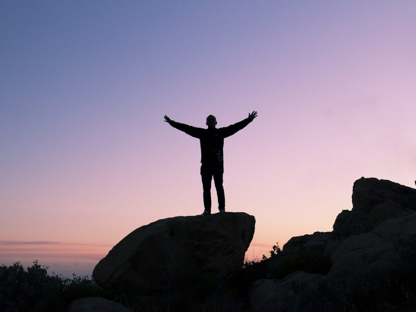 silhouette of person outstretched arms on a boulder