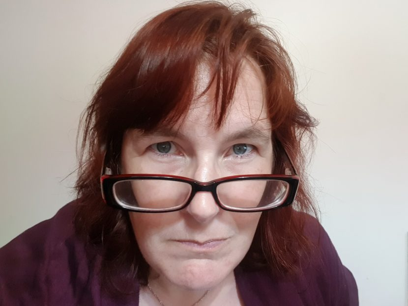 woman with red hair and plum shawl looking directly into the camera over red spectacles.