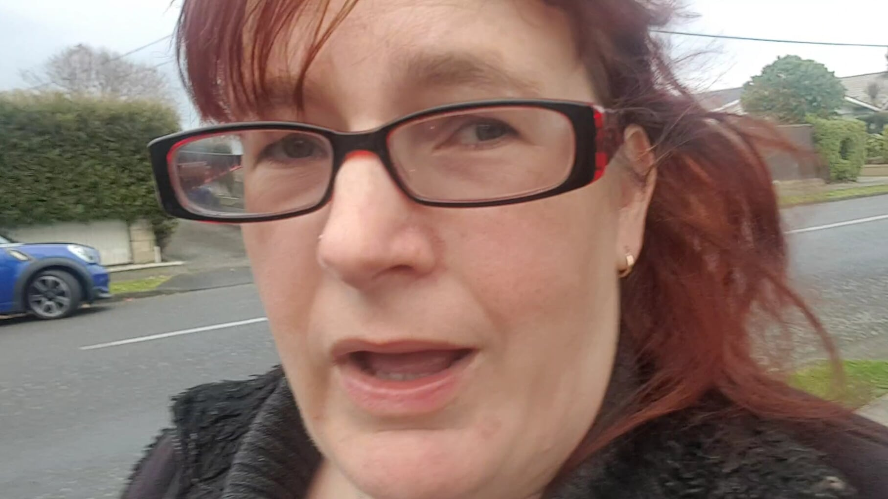 woman looking into the camera wearing glasses. She is outside in a street with a road in the background.