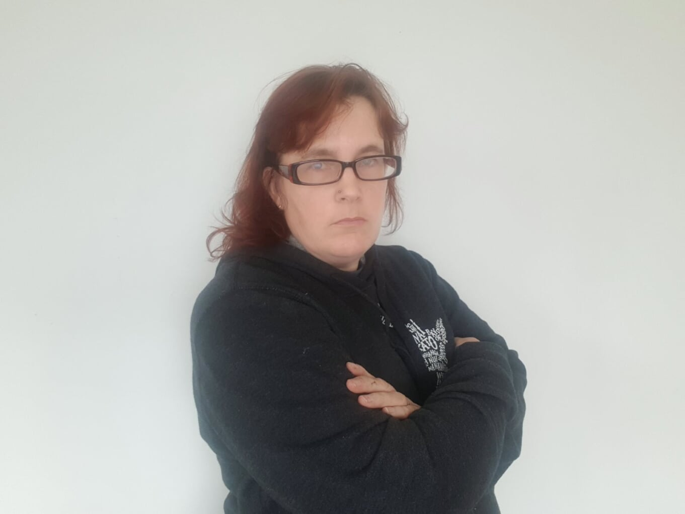 red haired woman in grey hoodie and glasses looking crossly into the camera with folded arms.