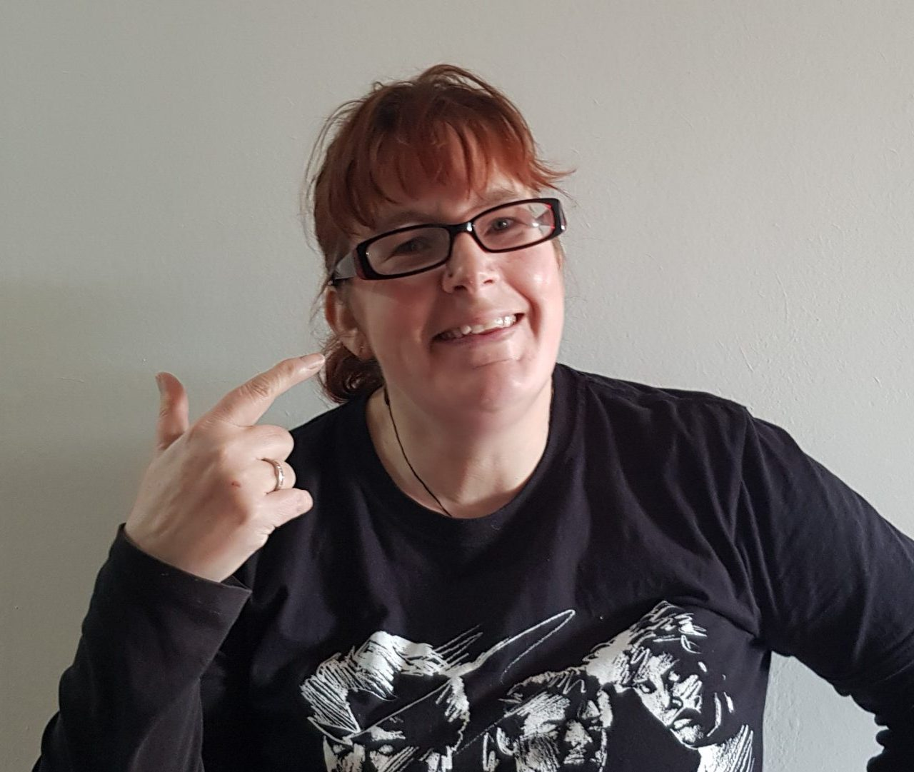 kitty fitton with red hair and glasses pinting aat herself and grinning.