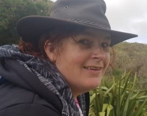 kitty smiling sideways at the camera in a brown hat with nz countryside in background.